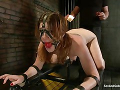 Cici Rhodes can't live without the dungeon. Belted to a board, tied and gagged the brunette receives a punishment with hot wax and spanking. Her master removes a metal plug from her ass, then re-inserts it, attaching a rope from it to her head. A sextoy runs over her pussy, making her want to cum, but can't yet.
