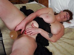 She's mature, hot and has a pair of immense scoops that need a hard schlong between them. Meet Leah, a plump older whore that's masturbating in front of us. Leah uses her big bad dildo to fill her pussy and has a great time doing it. The cunt rubs her scoops while masturbating and groans with delight wishing for a real 10-Pounder